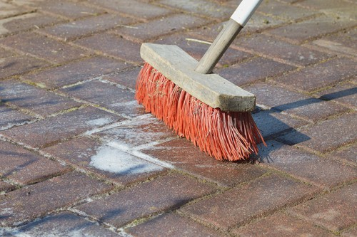 Cleaning patio with detergent and brush