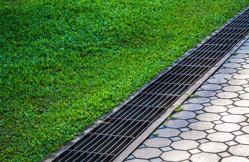 Drain to collect water before reaching lawn