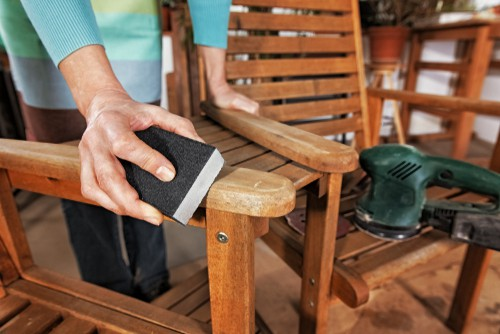Lady maintaining a loveseat by sanding it down getting it ready to paint with oil