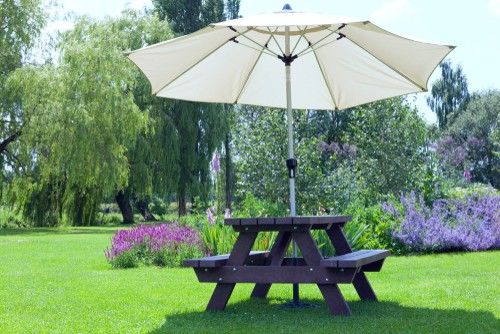 Garden picnic table with parasol in centre hole
