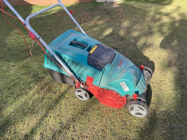 Bosch 1100 AVR Verticutter side view about to start scarifying and aerating the lawn