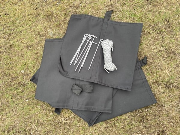 Weight bags to fill with sand, pegs and guide ropes to secure gazebo