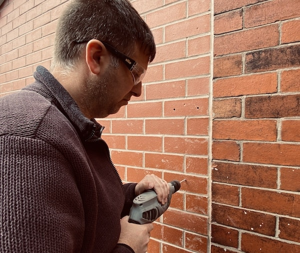 Drilling holes in brick wall to attach hose pipe
