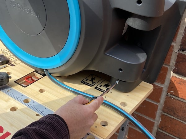 Undoing small screw to separate hanging bracket from main hose reel
