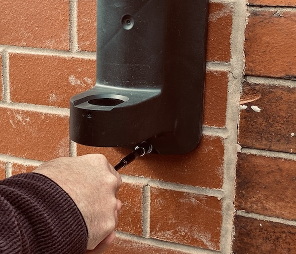 Tightening final screw into wall mounted hose pipe bracket