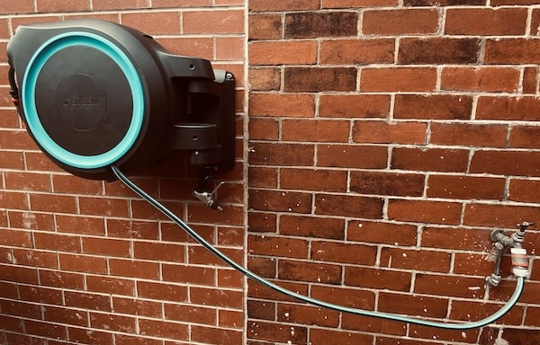 Wall mounted hose pipe fixed to the wall and ready to use