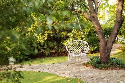 Outdoor hanging hammock chair hanging from tree in garden