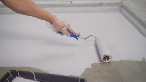 Painting small garage floor with a small hand roller
