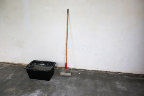 Large paint bucket and roller ready for painting garage floor