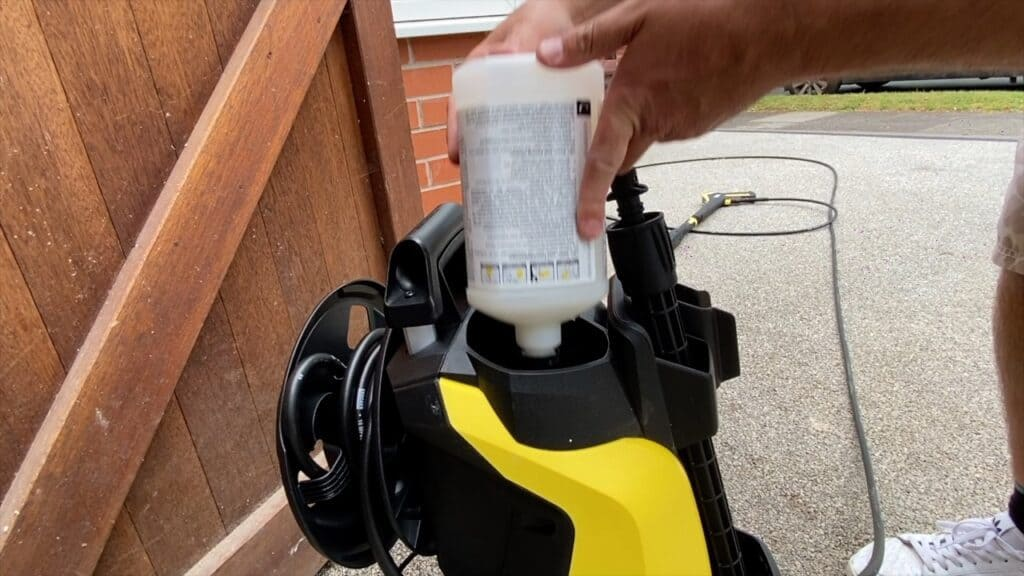 Inserting the detergent bottle into the top of the pressure washer using the Plug n Play system.