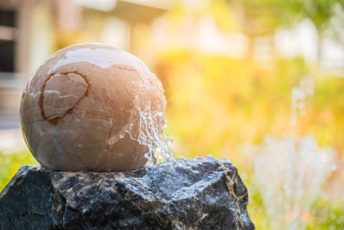 Sphere water feature sat on top of rock as feature