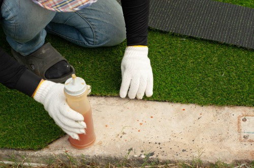 Preparing ground for artificial grass and fastening it down with glue