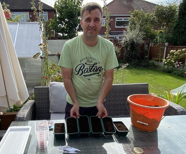 Seed trays filled with seed compost ready for sowing winter pansy seeds